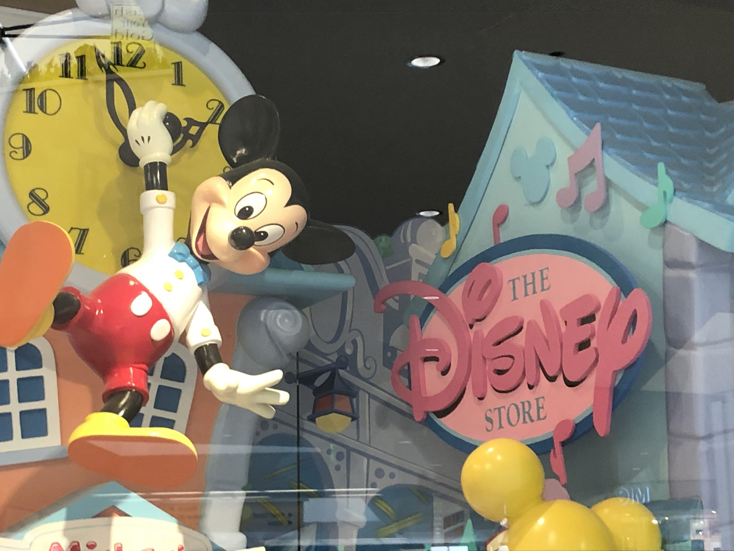 mickey mouse in front of mickey's toontown disney store front
